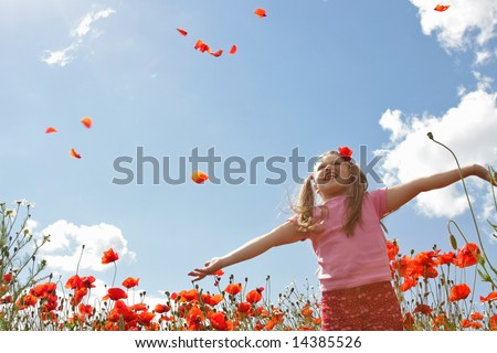 Little girl meadow throwing poppy petals, blue sky in background