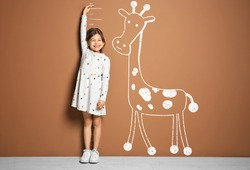 Little girl measuring height and drawing of giraffe near brown wall