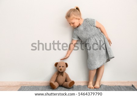 Little girl measuring height of toy bear near wall