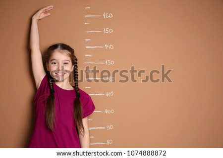 Little girl measuring her height on color background #1074888872