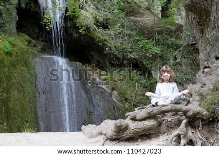 little girl meditate by the waterfall