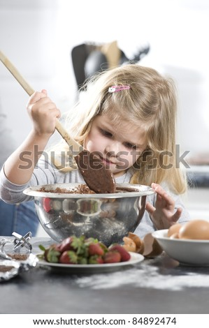 little girl mixing a chocolate cake in a silver bowl