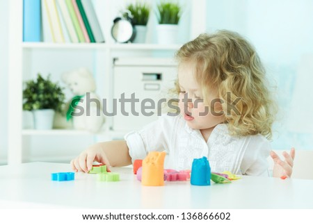 Little girl modeling with clay at kindergarten