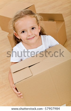 Little girl moving into a new home with cardboard box  - top view - stock photo