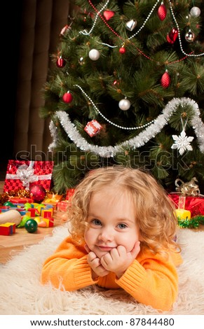 Little girl near Christmas tree