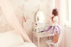 Little girl near the mirror.  A little fashionista in the bedroom.