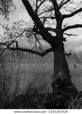 little girl next to a tree next to lake with reeds black and white