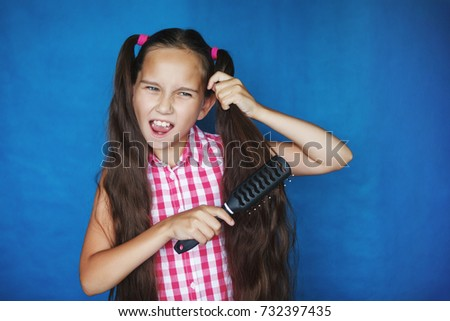 Little girl on a blue background combing her long hair #732397435