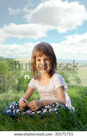 Little girl on a meadow with dandelion.
