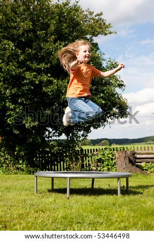 Little girl on a trampoline in a garden, in the background a fence and some landscape