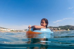 Little girl on an inflatable in the sea