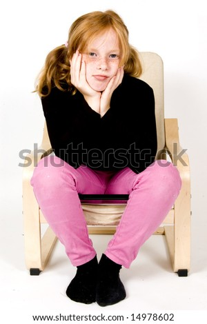 little girl on chair is looking bored - stock photo