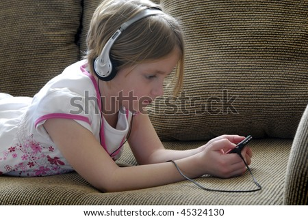 Little girl on couch listening to mp3 music with earphones