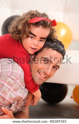 little girl on daddy's back celebrating Halloween