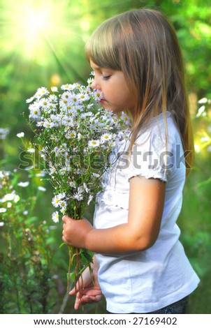 Little girl on meadow with wild flower
