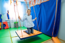 little girl on Platform suspended projectile for classes on method of sensory integration and correctional and developmental technologies. games and educational activities. therapeutic exercise.