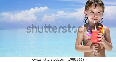 little girl on the beach drinking exotic cocktail