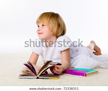 little girl on the floor studying with books and paper
