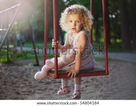 Little girl on the swing. - stock photo
