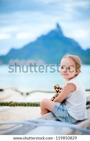 Little girl on vacation on Bora Bora island with Otemanu mountain silhouette on background