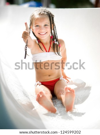 Little girl on water slide at aquapark show the thumb - stock photo