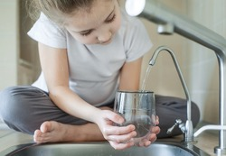 Little girl open a water tap with her hand holding a transparent glass. Kitchen faucet. Filling cup beverage. Pouring fresh drink. Hydration. Healthcare. Healthy lifestyle. World Water Day