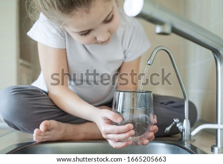 Little girl open a water tap with her hand holding a transparent glass. Kitchen faucet. Filling cup beverage. Pouring fresh drink. Hydration. Healthcare. Healthy lifestyle. World Water Day Foto stock ©