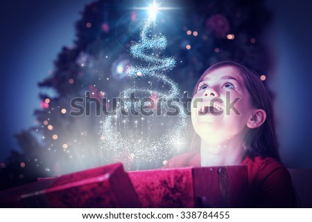 Stock Photo Little girl opening a magical christmas gift against christmas tree design