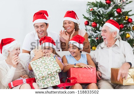 Little girl opening christmas present on couch with family