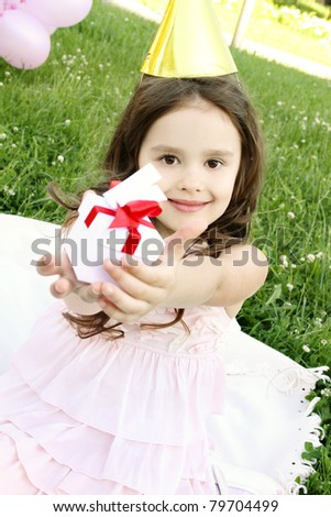Little girl outdoors celebrating birthday is happy and holding a gift box.
