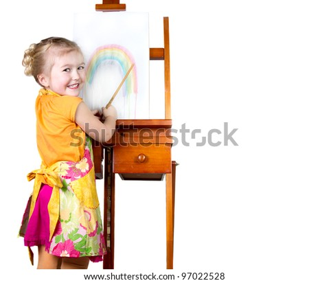 Little girl painting a rainbow on an easel, isolated on white