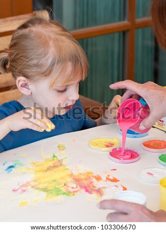 Little girl painting colors on hand