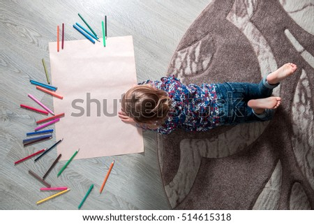Little girl painting, drawing. Child lying on the floor near crayons. Top view. Creativity concept. Unrecognizable. #514615318