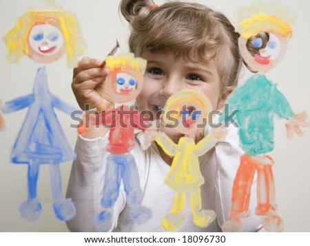 Little girl painting family on glass
