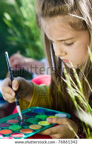 Little girl painting in nature - stock photo