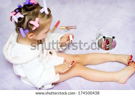 little girl painting nails while wearing hair-rollers, at home
