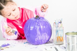 Little girl painting small craft pumpkin with purple acrylic paint.