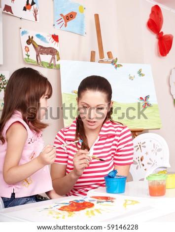 Little girl painting with teacher in preschool. - stock photo