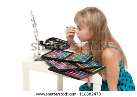 Little girl paints his face makeup, on white background