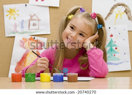 Little girl paints pictures in bright colors - stock photo