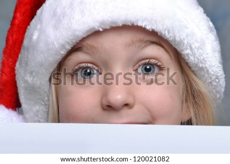 little girl peeking over a christmas list