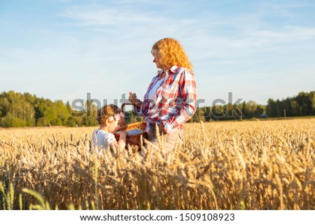 Little girl peeks into a wicker basket. A girl with red hair and a child stands on a wheat field. Picnic in the countryside, countryside. #1509108923