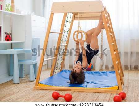 little girl performs gymnastic exercises on a wooden home sports complex stairs, rings and rope. Children's sports exercises. Physical education of children at home. Stock photo ©