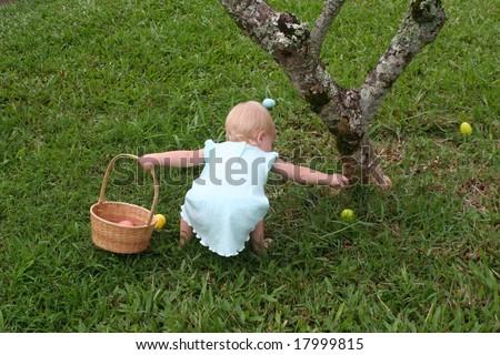 Little girl picking up Easter eggs