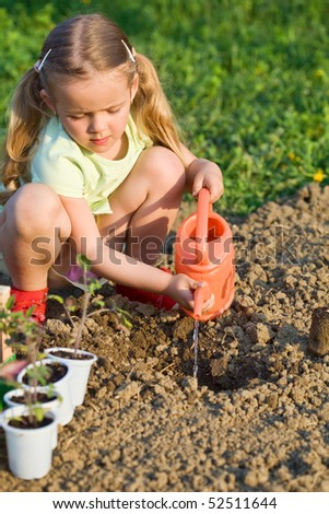 Little girl planting tomato seedlings - preparing the soil
