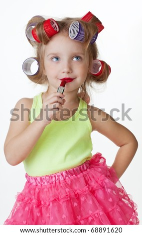 Little girl play big applying lipstick and wearing hair rollers