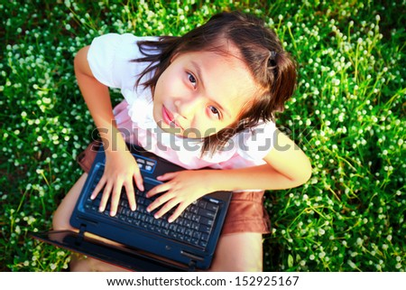 little girl play computer  on green grass