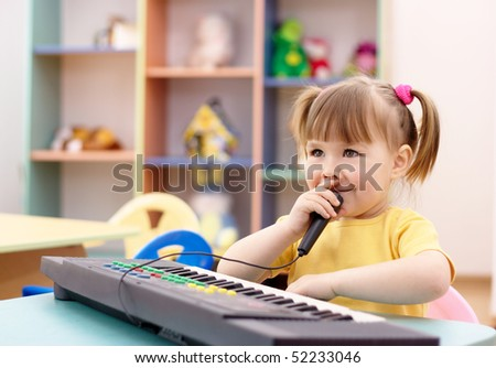 Little girl play on a piano and sing in preschool