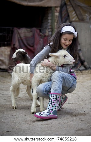 Little girl play with newborn lamb in a farmyard