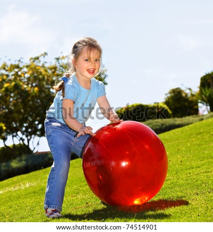 little girl play with red ball in the park